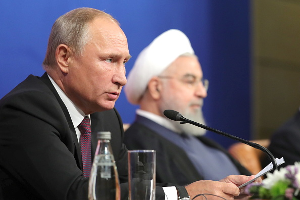Russia's President Vladimir Putin (L) and Iran's President Hassan Rouhani give a press conference after the third trilateral meeting aimed at facilitating peace process in Syria and held at an International Congress Centre in Tehran. (Getty)