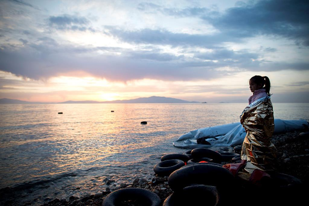 A small Syrian girl looks on during sunrise after arriving on an inflatable boat with other refugees, crossing the sea from Turkey to Lesbos, some 5 kilometres south of the capital of the Island, Mytelene on March 9, 2016 in Mytelene, Greece. (Getty)