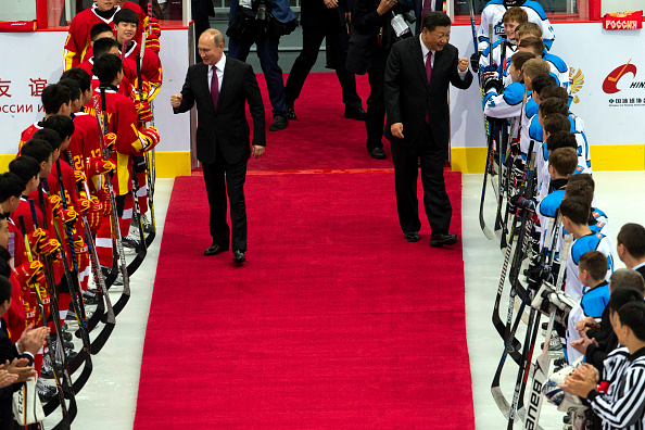 Russian President Vladimir Putin (C-L) and Chinese President Xi Jinping greet players from Chinese and Russian youth Ice Hockey teams before a friendly match on June 8, 2018 in Tianjin, China. (Getty)