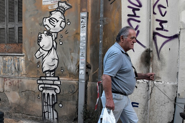 A man walks past a graffito depicting a bag of money with a euro currency symbol on a crumbling greek statue and column in Athens on September 12, 2018. (Getty Images)