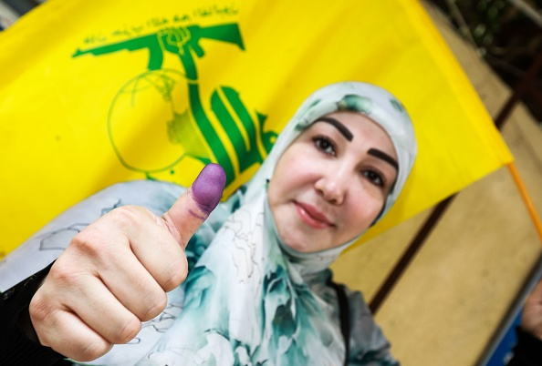 A Lebanese Shiite woman flashes her ink-stained thumb and waves a flag of the Shiite Hezbollah movement after voting at a polling station in the capital Beirut on May 6, 2018, as the country votes in the first parliamentary election in nine years. (Getty)