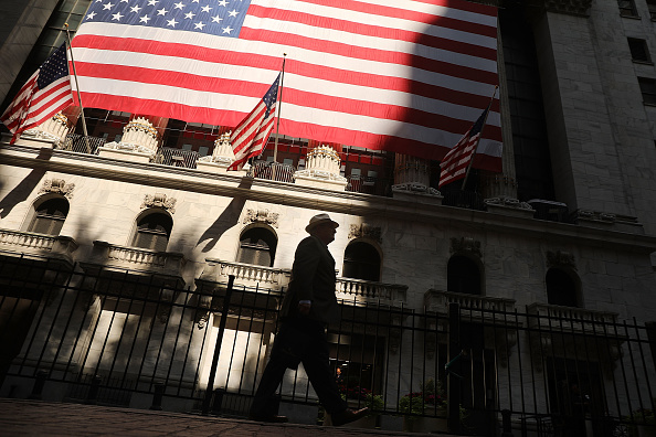 A man walks by the New York Stock Exchange (NYSE) on July 12, 2018 in New York City. As fears of a trade war eased with China, the Dow Jones Industrial Average rose 140 points in morning trading. (Getty)