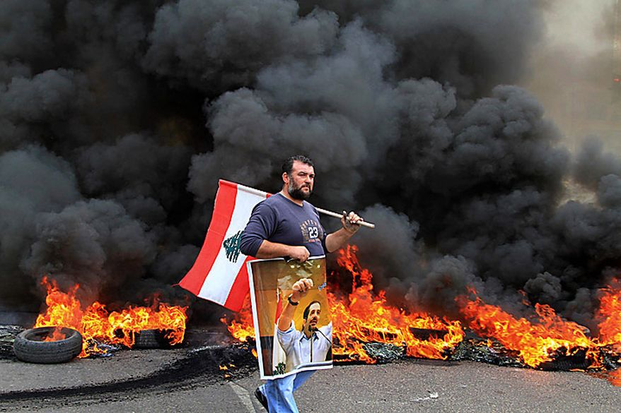 A protester carries a picture of outgoing Prime Minister Saad Hariri and a Lebanese flag as he walks in front of burning tires in the southern port city of Sidon, Lebanon, Jan. 25, 2011. Sunnis protested the rising power of the Shi'ite militant group Hezbollah on Tuesday, burning tires and torching a van belonging to Al Jazeera. (AP)